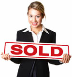 Happy young businesswoman holding sold sign board against white